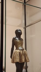 Momento Mori: murdered child ballerina, entombed in her glass case, face to the light.